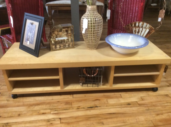 We also consign contemporary furniture like this sleek rolling coffee table. Matching shelving unit also available.