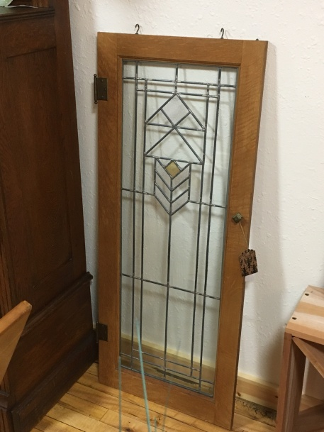 Frank Lloyd Wright style leaded glass window in craftsman style oak wooden cupboard frame.